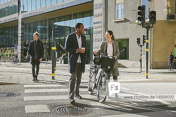Full length of smiling man and woman talking while walking with electric bicycle on crosswalk against building in city
