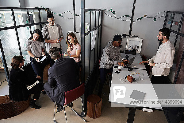 High angle view of entrepreneurs discussing with bank managers in creative office
