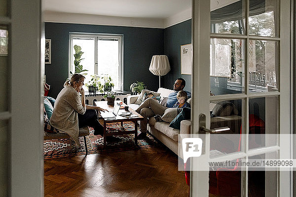 Family using various technologies in living room seen through doorway at home