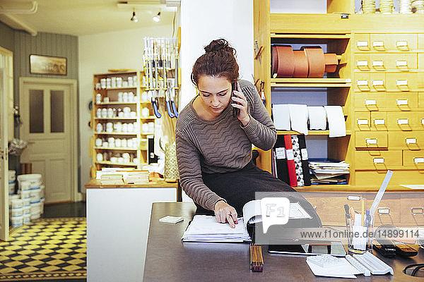 Junge Verkäuferin betrachtet Dokument  während sie im Baumarkt sitzt und mit dem Handy telefoniert
