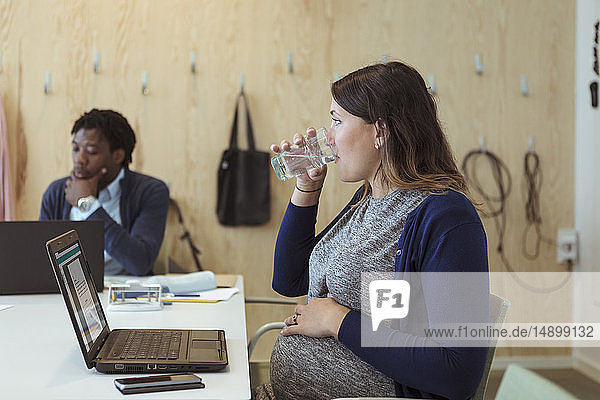Pregnant businesswoman drinking water while sitting with laptop in meeting