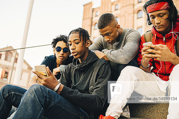 Male friends using mobile phones while sitting in city
