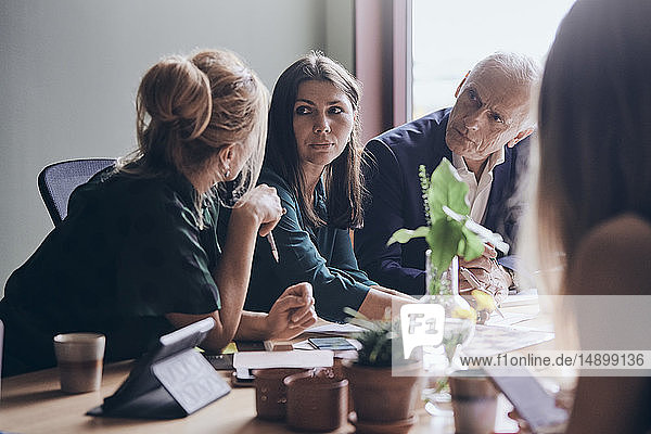 Female professionals planning strategy with businessman sitting at conference table during meeting in board room
