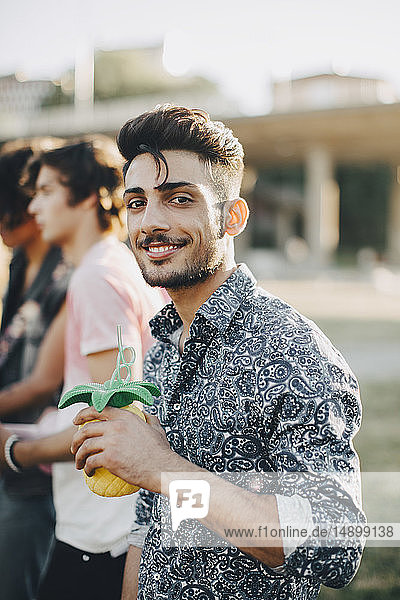 Porträt eines lächelnden jungen Mannes  der im Konzert mit einem Freund einen Drink genießt