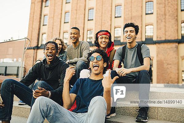 Happy male friends sitting in city