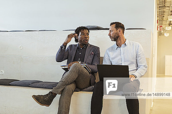 Serious businessman gesturing while talking to mature male colleague in office