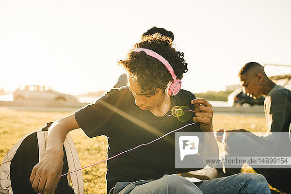 Teenage boy listening music on headphones while sitting with friend during sunny day