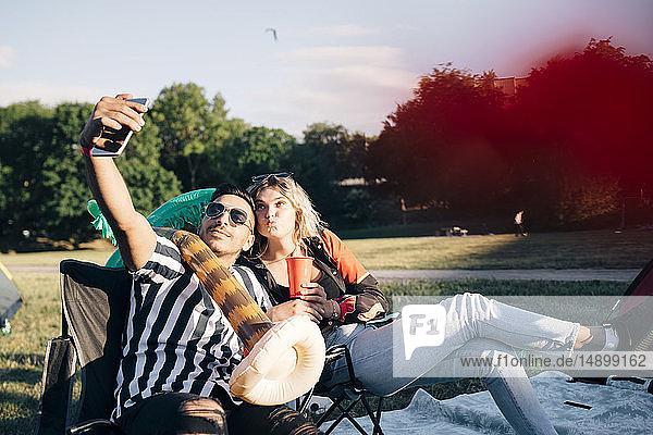 Freunde nehmen Selfie auf Smartphone  während sie bei einer Veranstaltung mit Ballon sitzen