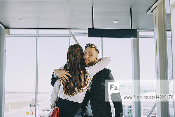 Smiling businessman greeting while embracing businesswoman in corridor at airport
