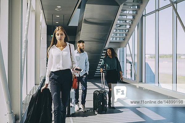 Junge Geschäftsfrau geht vor Kollegen auf dem Korridor des Flughafens