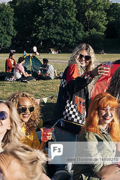 Lächelnde Freunde  die am sonnigen Tag beim Zelten einen Drink genießen  im Konzert