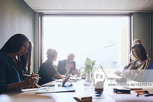 Reife männliche Manager planen Strategie mit Geschäftsfrau durch weibliche Kollegen im Sitzungssaal