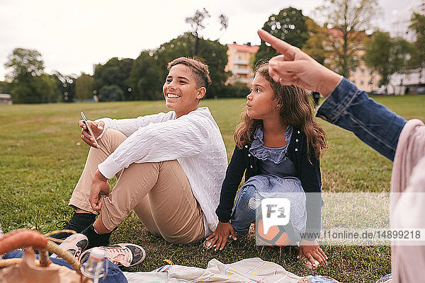 Siblings looking away while sitting on grassy field in park during picnic