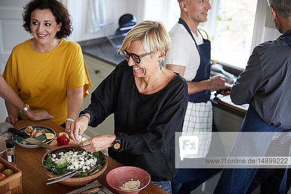 Schrägansicht auf glückliche Freunde  die zu Hause in der Küche gemeinsam Essen zubereiten