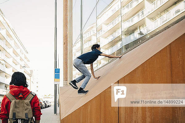 Carefree teenage boy climbing on wall while friend standing at sidewalk in city