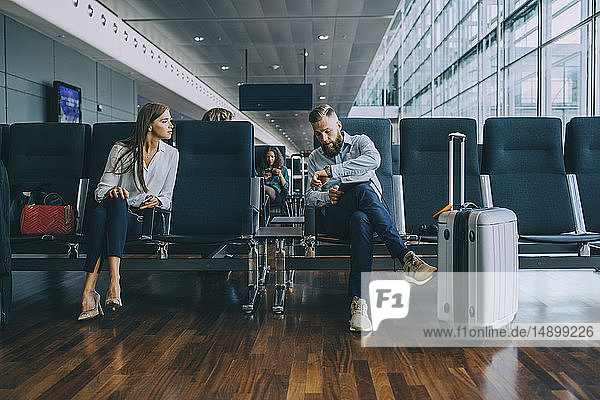Businessman telling time to businesswoman waiting in airport departure area