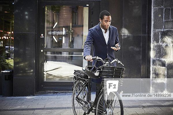Junger männlicher Pendler  der mit einem Smartphone unterwegs ist und mit einem Elektrofahrrad gegen ein Gebäude in der Stadt fährt