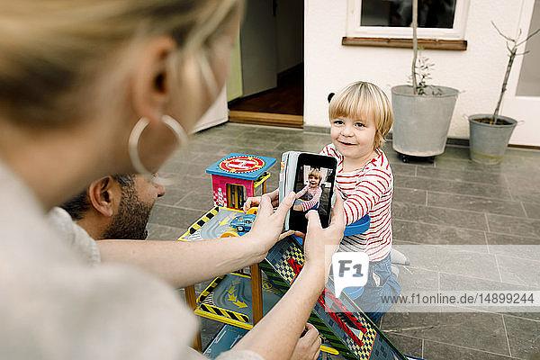 Mutter fotografiert lächelnde Tochter beim Spielen mit Spielzeugautos auf der Veranda
