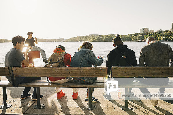 Friends eating take out food while sitting side by side on bench in city during sunny day