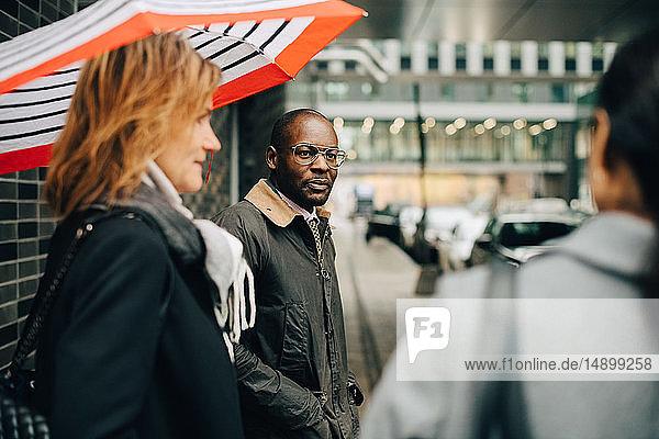 Kollegen unterhalten sich im Stehen auf dem Bürgersteig in der Stadt