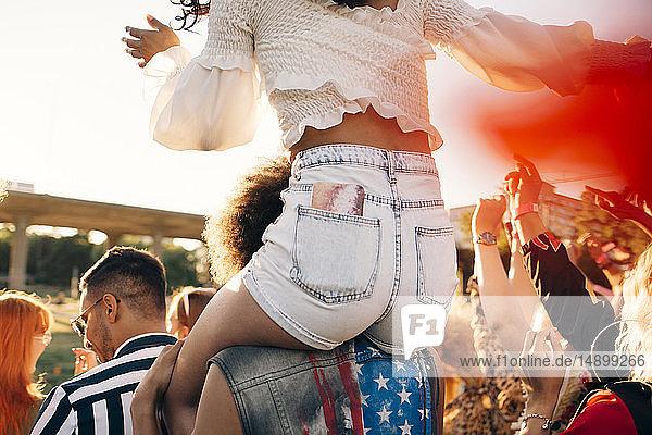 Mann trägt Freund auf der Schulter  während er beim Musikfestival genießt