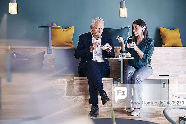 Geschäftsmann und Geschäftsfrau in voller Länge beim Essen in der Büro-Cafeteria