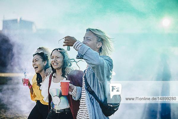 Fröhliche Freunde genießen Getränke beim Spaziergang inmitten von Pulverfarbe beim Musikfestival