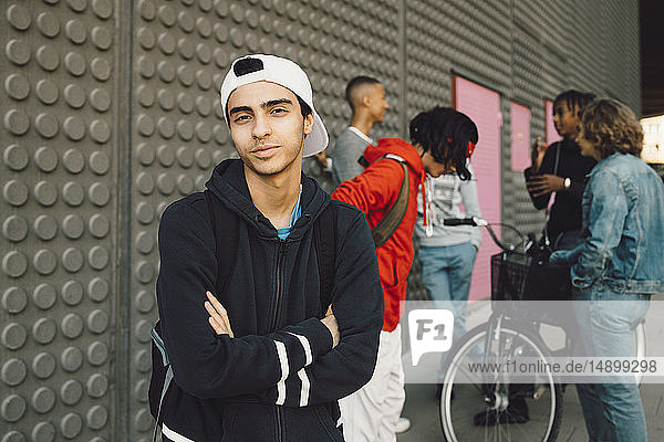 Portrait of confident young man with friends talking in background on footpath