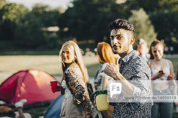 Porträt eines lächelnden Mannes  der während eines Konzerts mit Freunden gestikuliert