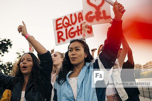 Frauen mit Transparenten  die gemeinsam für gleiche Rechte gegen den Himmel protestieren
