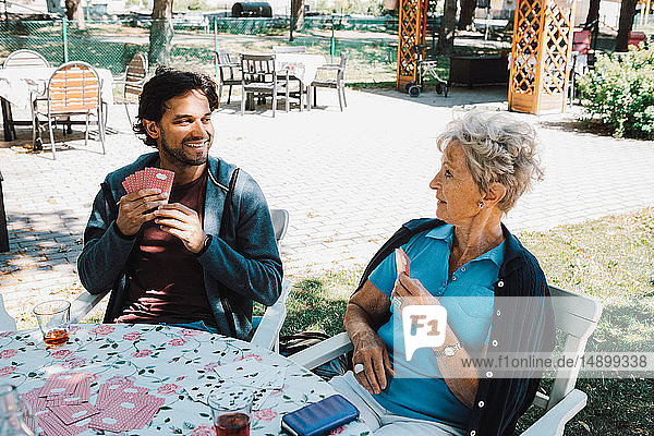 Retired senior woman playing cards with smiling male caretaker sitting at table in back yard