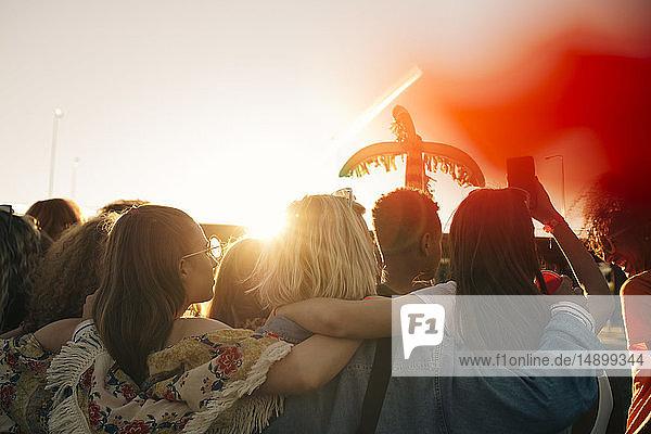 Rückansicht von Freunden  die im Sommer ein Musikfestival gegen den Himmel genießen