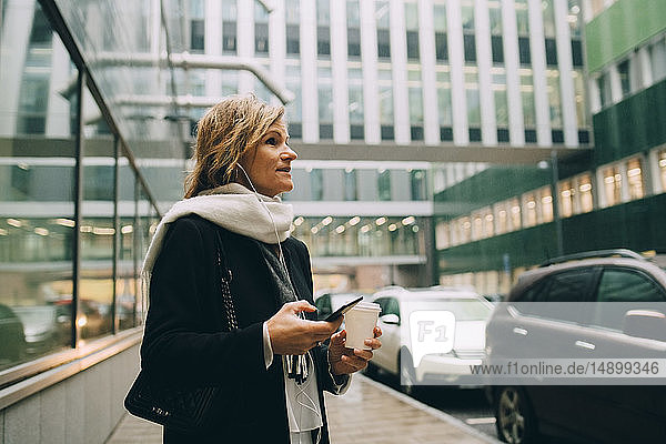 Businesswoman with coffee and smart phone looking away while standing on sidewalk against modern building in city
