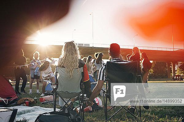 Rückansicht eines Mannes und einer Frau  die beim Musikfestival auf Stühlen sitzend Händchen halten