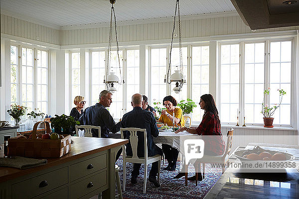 Friends having lunch in dining room at home during social gathering