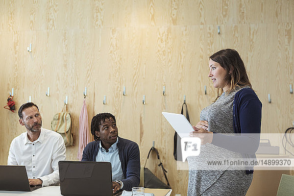 Pregnant woman discussing over digital tablet with male colleagues in meeting