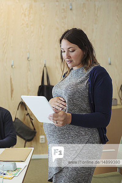 Pregnant professional looking at digital tablet in workplace