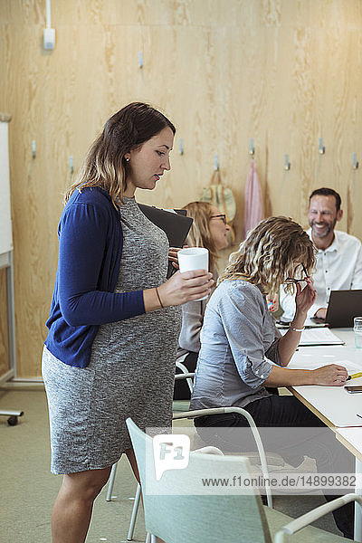 Pregnant businesswoman walking towards conference table in meeting