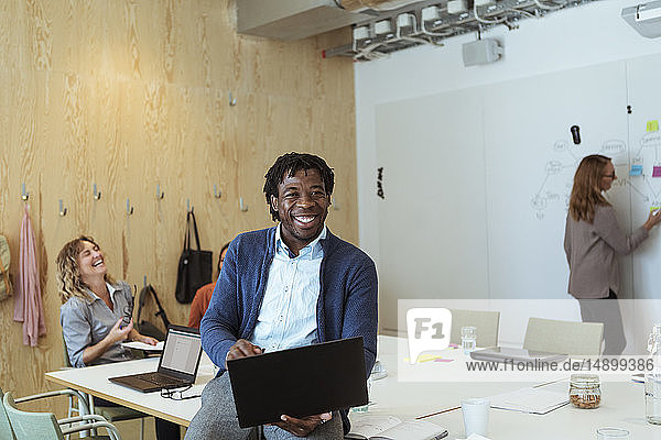 Smiling young businessman using laptop at conference table in board room
