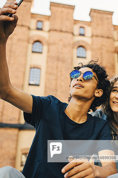 Fashionable teenage boy taking selfie with friend in city