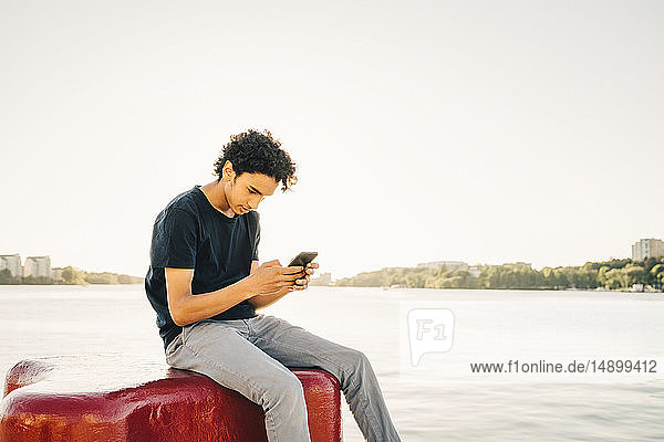 Teenage boy using mobile phone while sitting on bollard by river against clear sky during sunny day