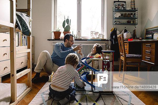 Vater und Töchter spielen zu Hause im Schlafzimmer