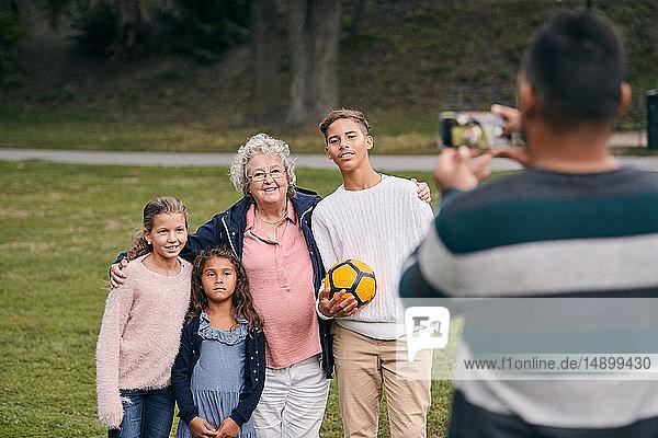 Rückansicht eines Mannes  der während eines Picknicks glückliche Großmutter und Enkelkinder im Park fotografiert