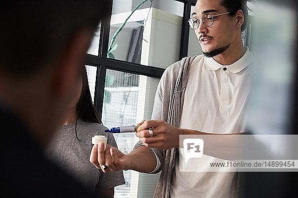 Männlicher Unternehmer erklärt Projekt bei Treffen im Kreativbüro