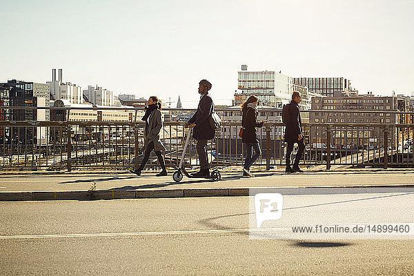 Männer und Frauen in voller Länge auf der Brücke in der Stadt