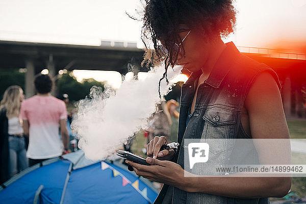 Seitenansicht eines jungen Mannes  der raucht  während er bei einer Musikveranstaltung ein Mobiltelefon benutzt