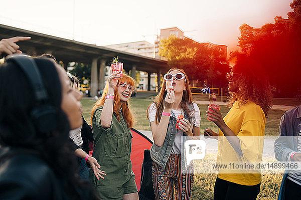 Freunde genießen im Sommer während des Musikfestivals Getränke und blasen Seifenblasen