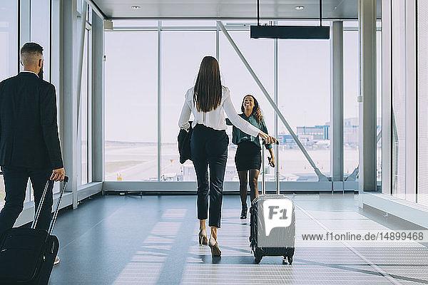 Lächelnde Geschäftsfrau geht auf eine Kollegin im Korridor des Flughafens zu