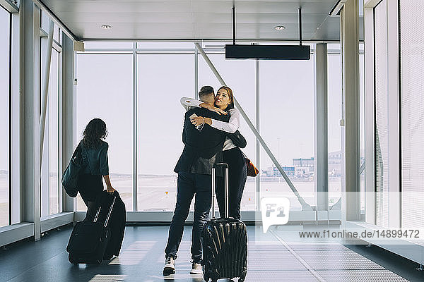 Businesswoman walking by colleagues greeting in corridor at airport