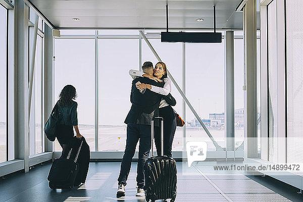 Geschäftsfrau geht an Kollegen vorbei und begrüßt sie im Korridor des Flughafens